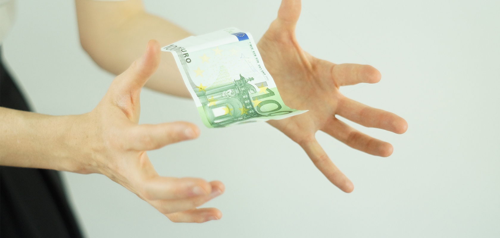 A Euro note slipping out of a woman's hands